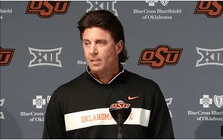 Oklahoma State Football Coach Who Wore an OAN Shirt Takes $1M Pay Cut After Backlash